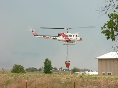 A white and red CDF helicopter taking off with a suspended water bag.